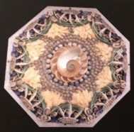octagonal shadow box containing a temple with a kaleidoscope design of colorful, small shells, twigs, sand, chips of shells