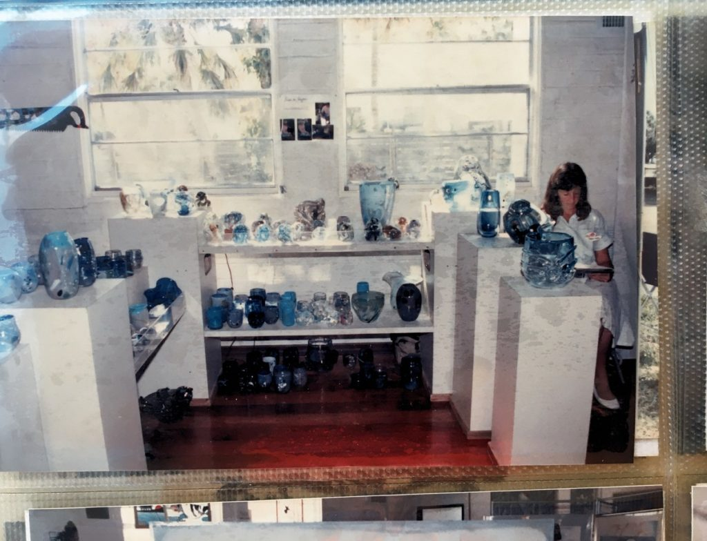 1988-89 woman sitting next to pottery display